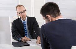 Problemi nel luogo di lavoro: critico del capo il suo impiegato a causa della sua b Immagine Stock