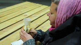 Problemi sanitari, obesità Donna grassottella povera che mangia hamburger grasso e che beve tè video d archivio