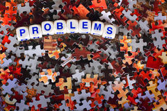 Problems. Dice spelling out the word problems sits on top of red and gray scattered puzzle pieces Stock Photos