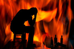 Problems with alcohol. Silhouette of a man on a background of fire Stock Photography