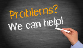 Problems - we can help - female hand with chalk writing text. On blackboard stock photography