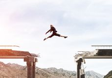 Problems and difficulties overcoming concept. Business woman jumping over huge gap in concrete bridge as symbol of overcoming challenges. Skyscape and nature Stock Image