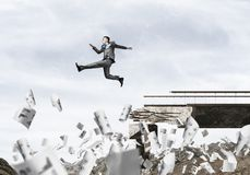 Problems and difficulties overcoming concept. Businessman jumping over gap in bridge among flying papers as symbol of overcoming challenges. Skyscape and nature Stock Image