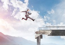 Problems and difficulties overcoming concept. Businessman jumping over huge gap in concrete bridge as symbol of overcoming challenges. Skyscape and nature view Royalty Free Stock Photos