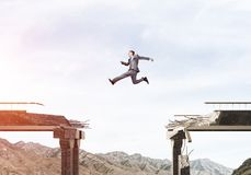 Problems and difficulties overcoming concept. Businessman jumping over huge gap in concrete bridge as symbol of overcoming challenges. Skyscape and nature view Stock Photo
