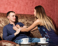 Problems in family relationships, a young couple sitting on the couch. man hurt, he turned away from the woman Stock Images