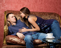 Problems in family relationships, a young couple sitting on the couch. man hurt, he turned away from the woman Royalty Free Stock Images