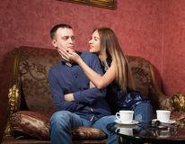 Problems in family relationships, a young couple sitting on the couch. man hurt, he turned away from the woman Royalty Free Stock Photos