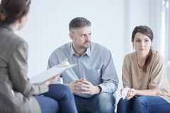 Problems in marriage. Worried couple with problems in marriage talking with psychologist Stock Photography