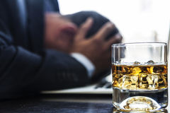 Problems On My Head. Man having problems, with a glass of alcohol near him royalty free stock image