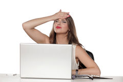 Problems in the office. Young and worried beautiful business woman sitting at her desk with laptop and having a problem Royalty Free Stock Images