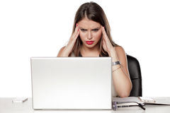 Problems in the office. Young and worried beautiful business woman sitting at her desk with laptop and having a problem Stock Photo