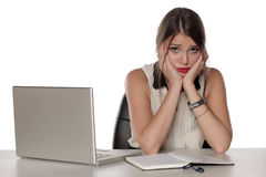 Problems in the office. Young and worried beautiful business woman sitting at her desk with laptop and having a problem Stock Photos