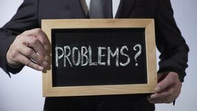Problems with question mark written on blackboard, businessman holding sign. Stock footage stock footage