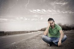 Problems on the road. Old photo of a young man sitting out of the road Stock Photography