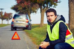 Problems on the road. Sad man having car trouble on the country road Royalty Free Stock Photos