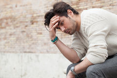 Problems and stress, stressed beautiful young man. A young man with his hands in the hair sitting on a bench outdoors. Concept of problems, stressful thoughts Stock Photography