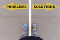 Problems vs Solutions text arrows on asphalt ground, feet and sh Stock Photo