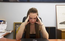 Problems at work and pain big in the head. A young girl at work.nProblems at work and pain big in the head royalty free stock photography