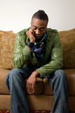 Problems of Young Men. A young african american sits on a couch, thinking about all the problems in his life Stock Image