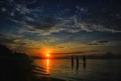 Probolinggo Indonesia 6 luglio 2016 Siluetta dei pescatori quando il sole aumenta sulla spiaggia immagini stock
