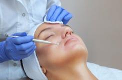 Procédure pour nettoyer la peau du visage avec un appareil en acier avec une cuillère des points noirs image stock