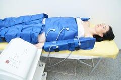Procédure pressotherapy dans la clinique Jeune fille sexy dans le costume photos libres de droits