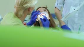 Procedimento clareando profissional dos dentes no escritório dental Dentista com assistente vídeos de arquivo
