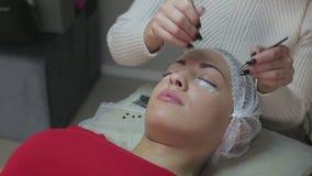 Procedimento da extensão da pestana Olho da mulher com pestanas longas video estoque