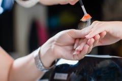 Procedimento do tratamento de mãos com os pregos de brilho Fotos de Stock Royalty Free