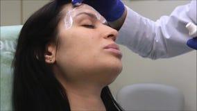 Procedimiento antienvejecedor: El dermatólogo del doctor aplica la crema en la cara de una morenita almacen de metraje de vídeo