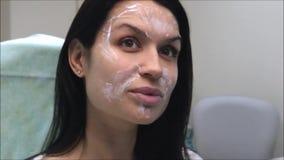 Procedimiento antienvejecedor: La muchacha morena hermosa está esperando el efecto de la crema sobre su cara metrajes