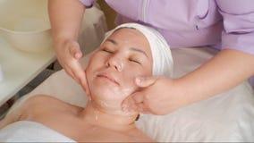 Procedimiento cosmético Cara del primer de una mujer asiática El cosmetologist aplica la crema al cuello y a los hombros femenino almacen de video