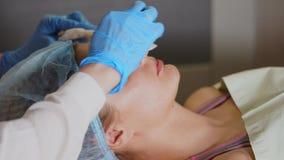 Procedimiento de la cosmetología La mujer que tiene máscara facial se aplica por el cosmetólogo metrajes