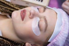 Procedimiento de la extensión de la pestaña Cara de la mujer con las pestañas falsas largas El cierre encima del tiro macro de la fotos de archivo