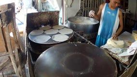 Procedimiento de la preparación de comida del Tercer mundo usando la bandeja del horno improvisada para hacer la envoltura del lu almacen de video