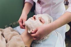 Procedimientos faciales Cosmet?logo experto agradable que saca una m?scara mientras que hace un procedimiento de la belleza fotos de archivo libres de regalías