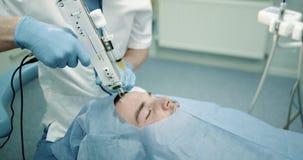Procedura del primo piano di medico facciale del vampiro che lavora con attenzione al fronte paziente con un'micro-agugliatura de video d archivio