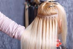 Procedura di estensioni dei capelli Il parrucchiere fa le estensioni dei capelli alla ragazza, bionda in un salone di bellezza Fu immagini stock libere da diritti