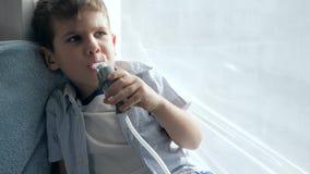 Procedura di infiammazione degli ossequi delle vie aeree tramite nebulizzatore in bambino che si siede sul davanzale a casa archivi video