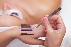 Procedura dla rzęs rozszerzeń w piękno salonie, rzęsy na ręce makijażu artysta Obrazy Royalty Free