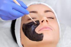 Procedura dla stosować czarną maskę twarz piękna kobieta Obraz Stock