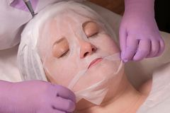 Procedura skóry odmładzanie w kosmetologii biurze Fachowy cosmetologist w lilych rękawiczkach gładzi maskę na zdjęcia royalty free