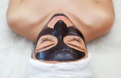 The procedure for applying a black mask to the face of a beautiful woman. Spa treatments and care of the cats in the beauty salon Royalty Free Stock Photography