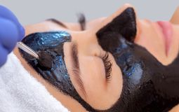 The procedure for applying a black mask to the face of a beautiful woman. Spa treatments and care of the cats in the beauty salon Stock Image
