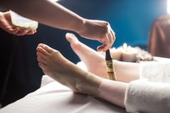 Procedure of applying clay mask on foot by beautician. Mud therapy. Close up of spa worker female hands aplying mad clay mask on female client foot in salon stock photo
