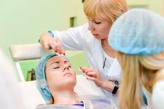 Procedure cosmetiche ragazza bella al ricevimento all'estetista Immagine Stock