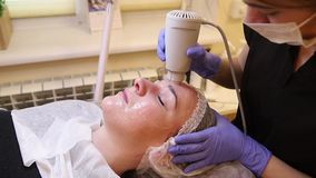 Procedure cryotherapy of the facial skin. Hardware cosmetology. Closeup picture of young woman with closed eyes getting cryomassage procedure in a beauty parlour stock video