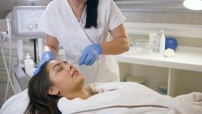 Procedure del salone della stazione termale, paziente della giovane donna sulle procedure cosmetiche di ringiovanimento al salone video d archivio