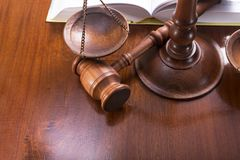 Procedure for litigation. Scales with a gavel and a book on a lacquered table royalty free stock photography